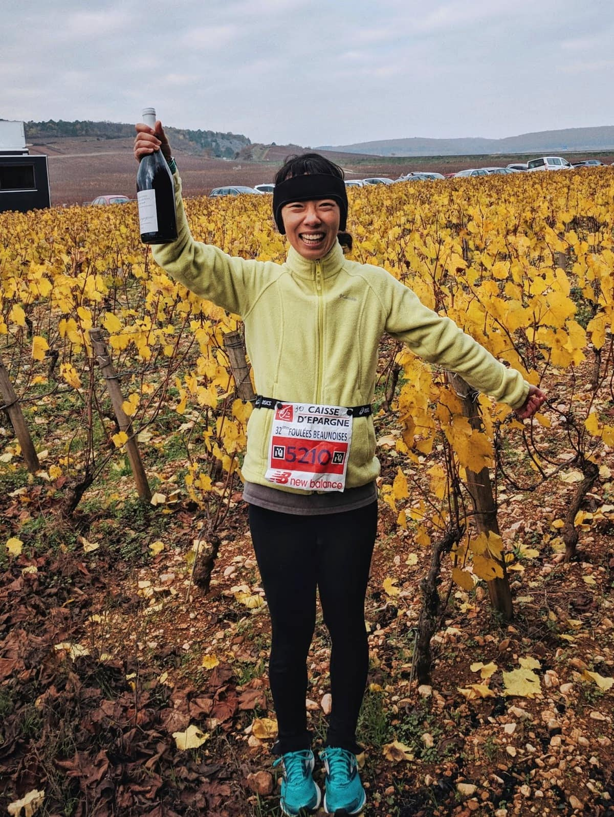 Posing in front of the vineyard with my finisher's bottle of wine at the 10km de Beaune