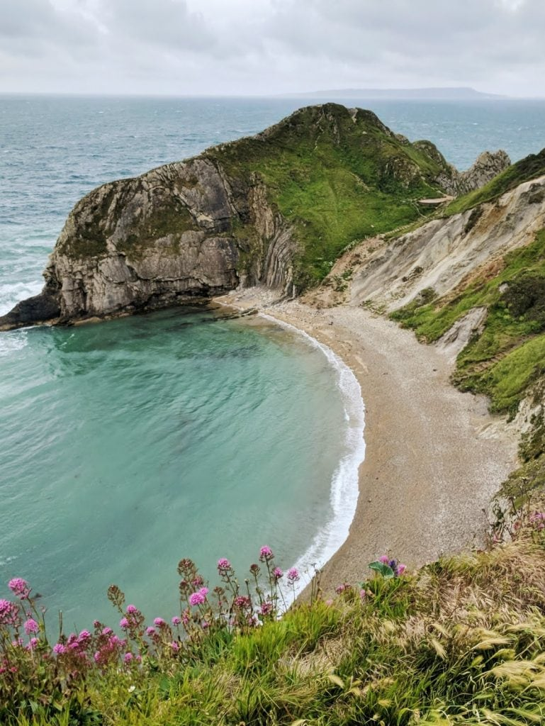 turquoise waters in a cove next to Durdle Door, a natural limestone arch