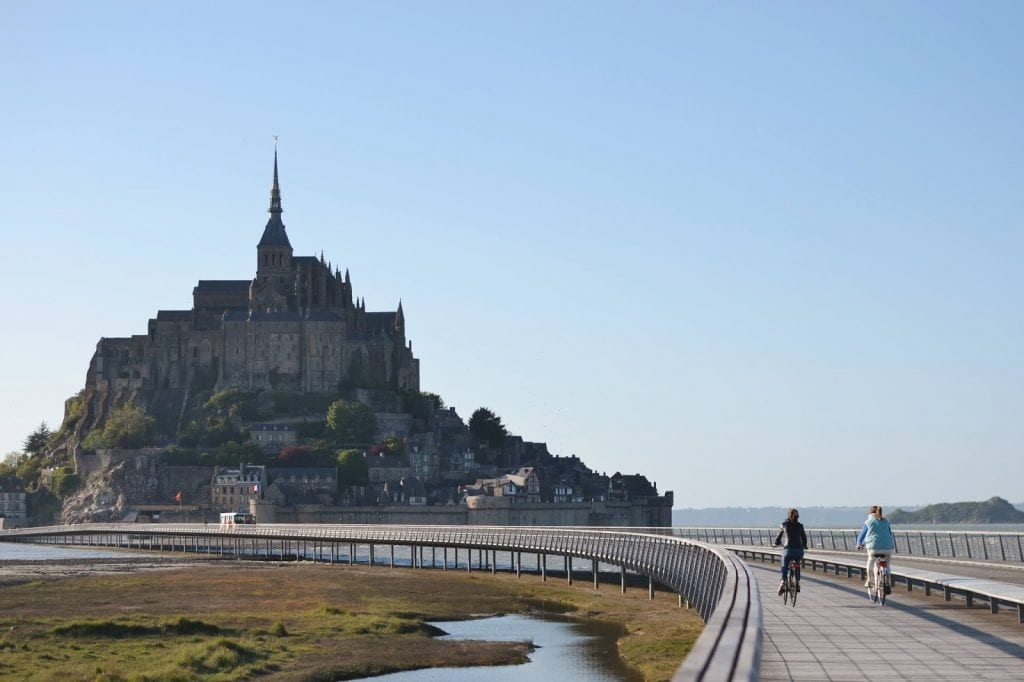 Mont Saint-Michel in Brittany, France with bikers approaching the long walkway