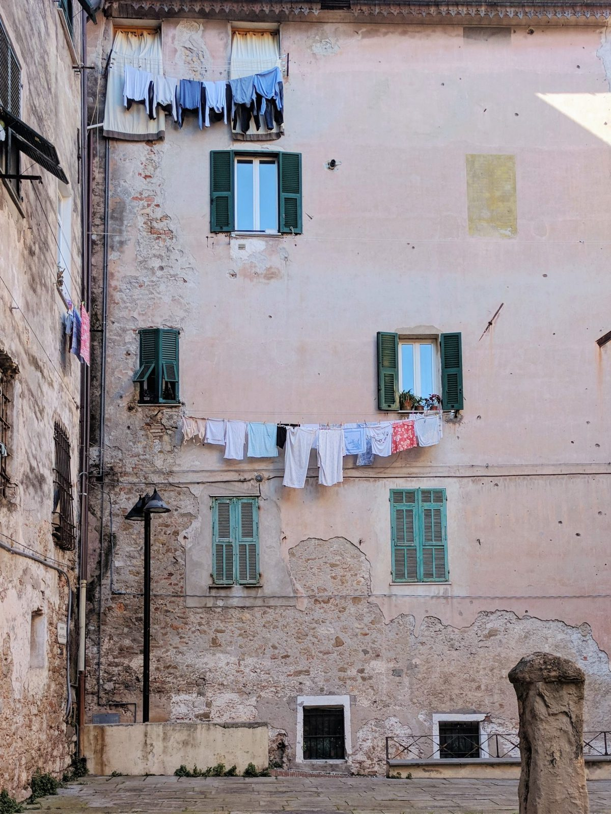 Laundry hanging on clotheslines outside of an old pink building in Ventimiglia, Italy