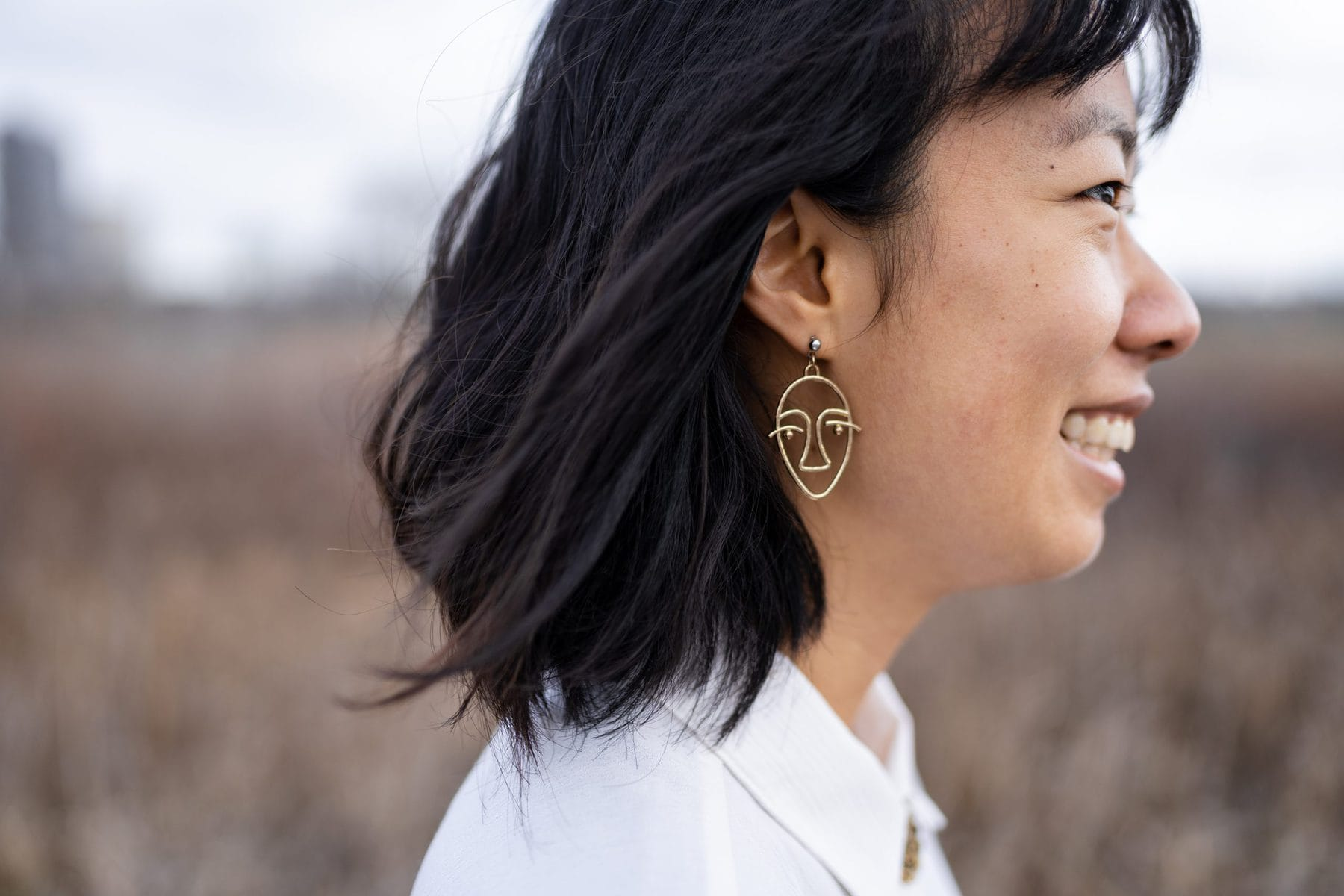 Wearing a thrifted vintage Laura Tyler shirt for $4 and face earrings. In this post, I discuss some common misunderstandings of sustainable fashion and offer practical tips to consume more consciously. | sustainable fashion | thrifted outfit