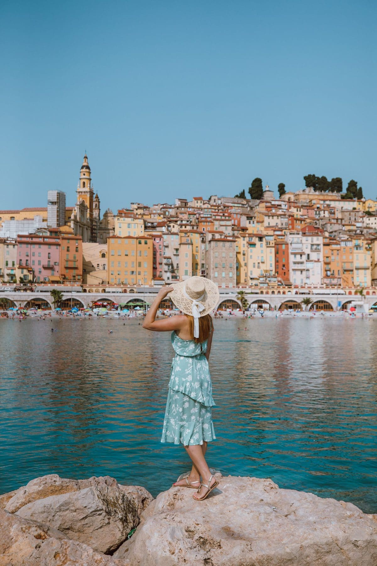 A woman in a blue dress and sunhat facing towards the colorful layers of houses across the water in Menton, France