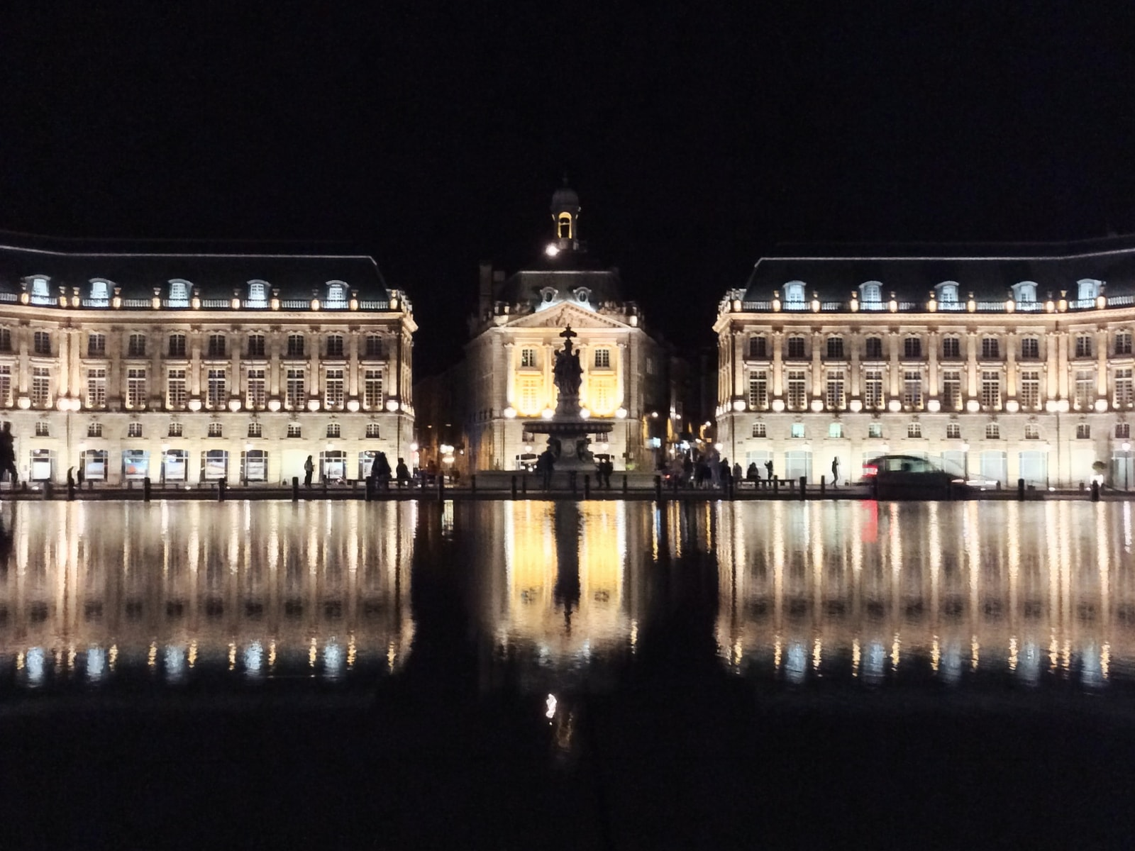 place de la bourse at night - the 18th century palace and its reflection in a pool of water at night