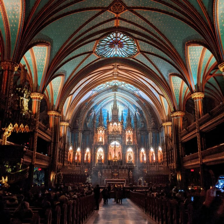 Inside the Notre-Dame Basilica in Montreal at night, with the arches and altar illuminated by golden light