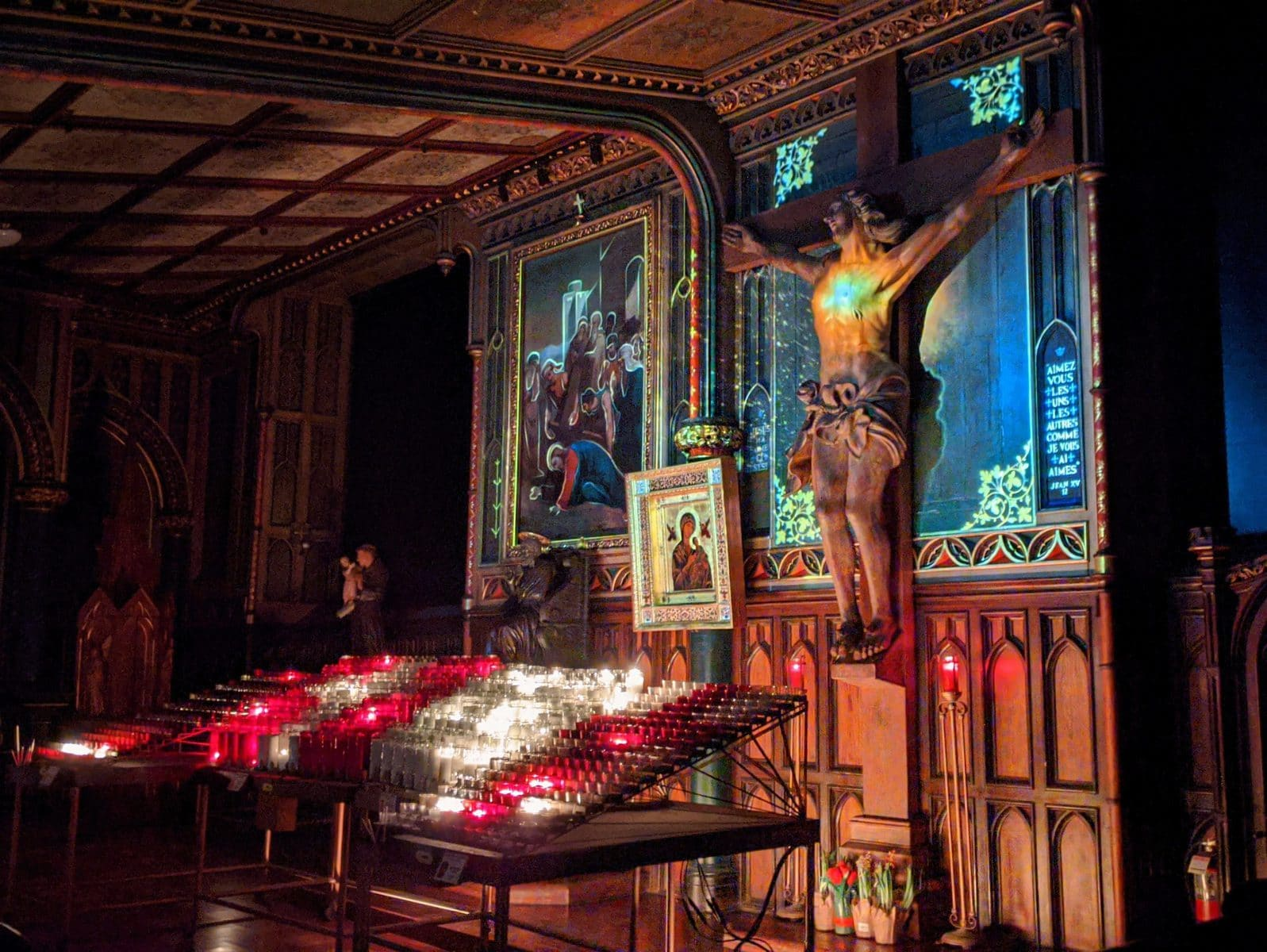 Illuminated sculpture of Jesus on the cross at Aura Montreal at the Notre-Dame Basilica