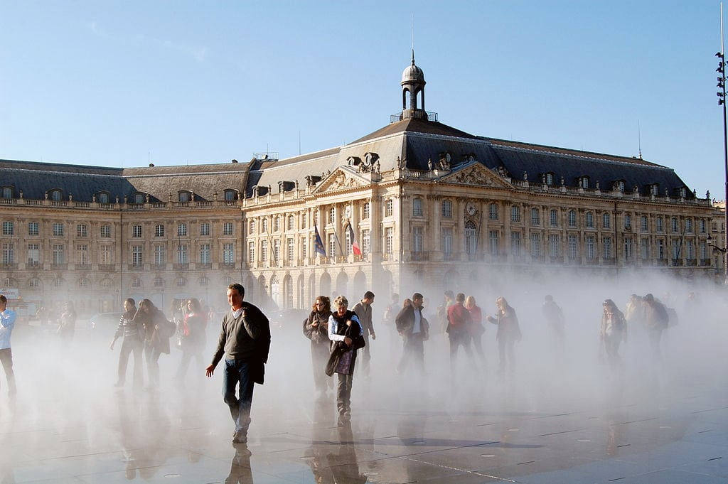 "Miroir d'eau in Bordeaux, France - mist coming from the ""mirror of water"" and people walking through with a backdrop of Place de la Bourse's 18th century buildings"