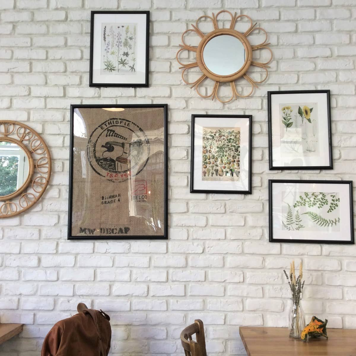 Pretty interior of Kitchen Garden vegetarian restaurant in Bordeaux, France - white brick walls, plants and gourds on the tables, flower-shaped mirrors and plant diagrams on the walls