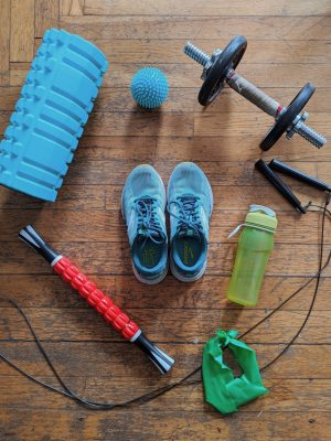 a bunch of fitness equipment laid out, including a foam roller, muscle stick, and resistance band