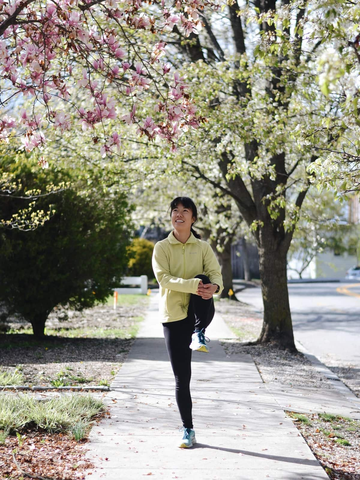 a runner stretching on a sidewalk lined with flowering spring trees