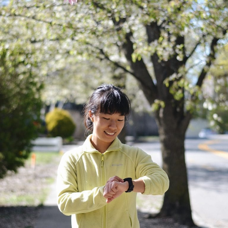 a runner looking at her watch on a sidewalk lined with flowering spring trees