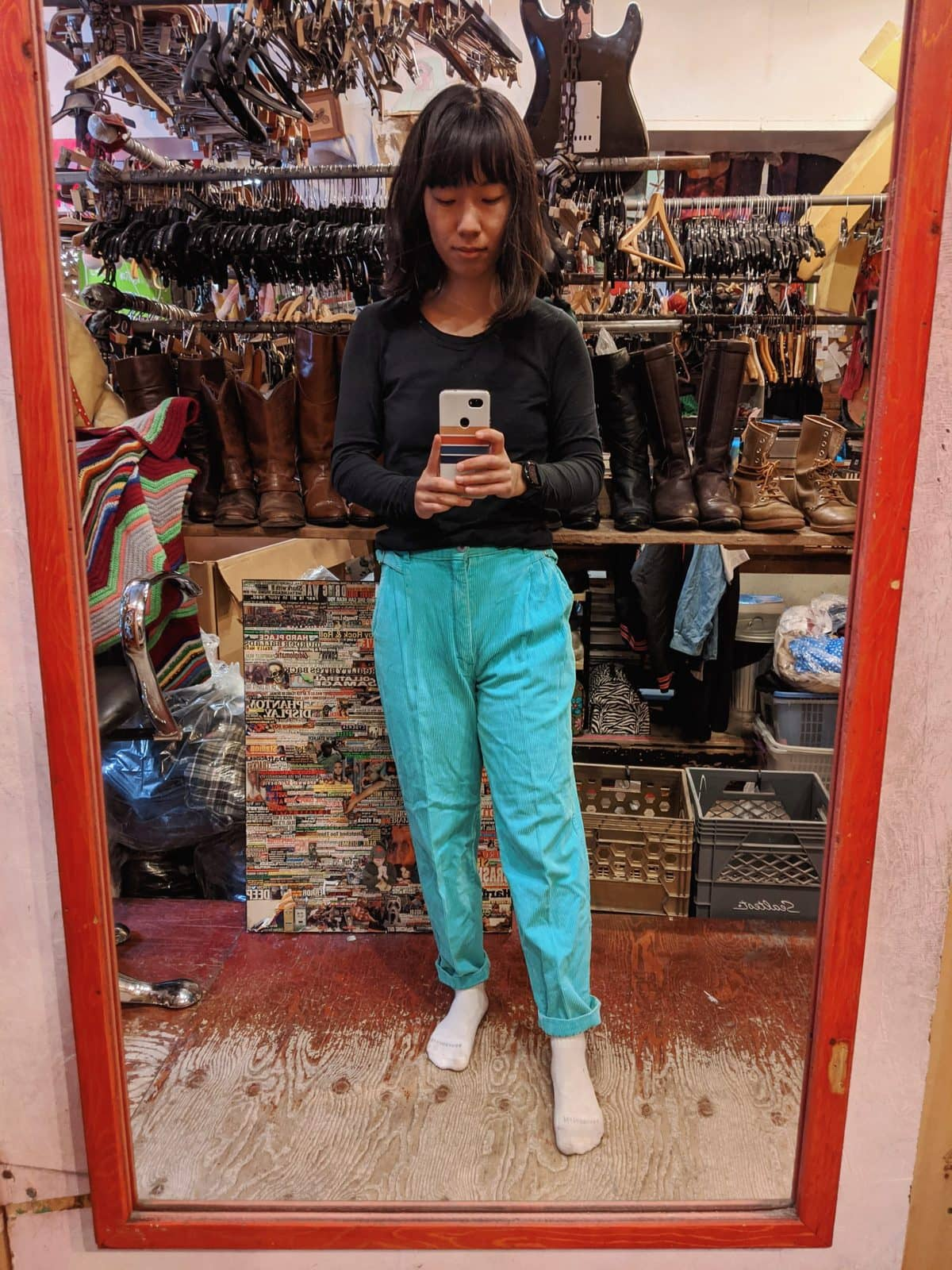 trying on bright blue pants in a thrift store