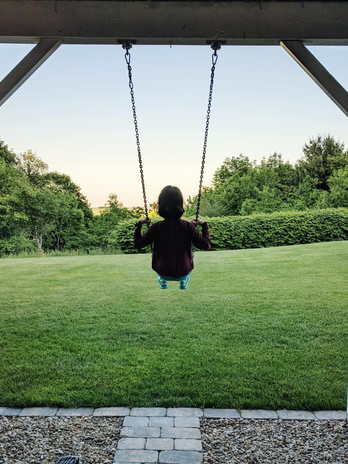 the silhouette of me swinging while overlooking a lush green field