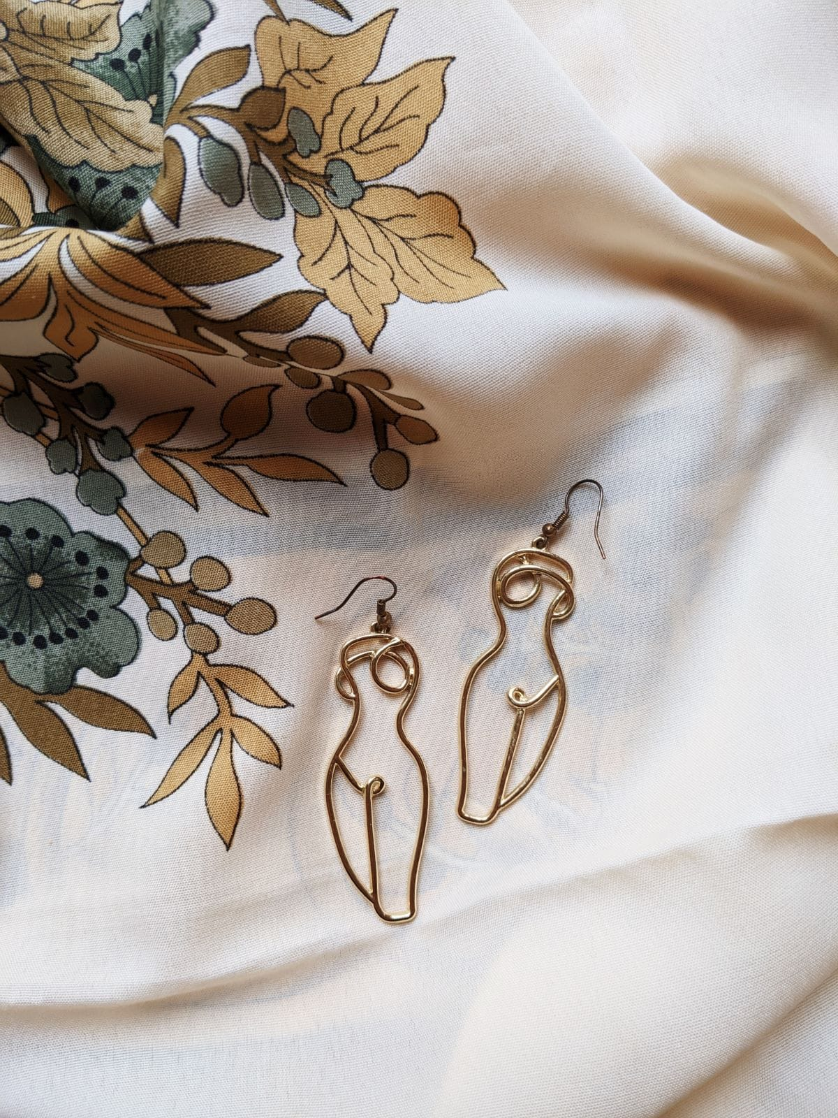 A pair of gold earrings outlining a nude female body