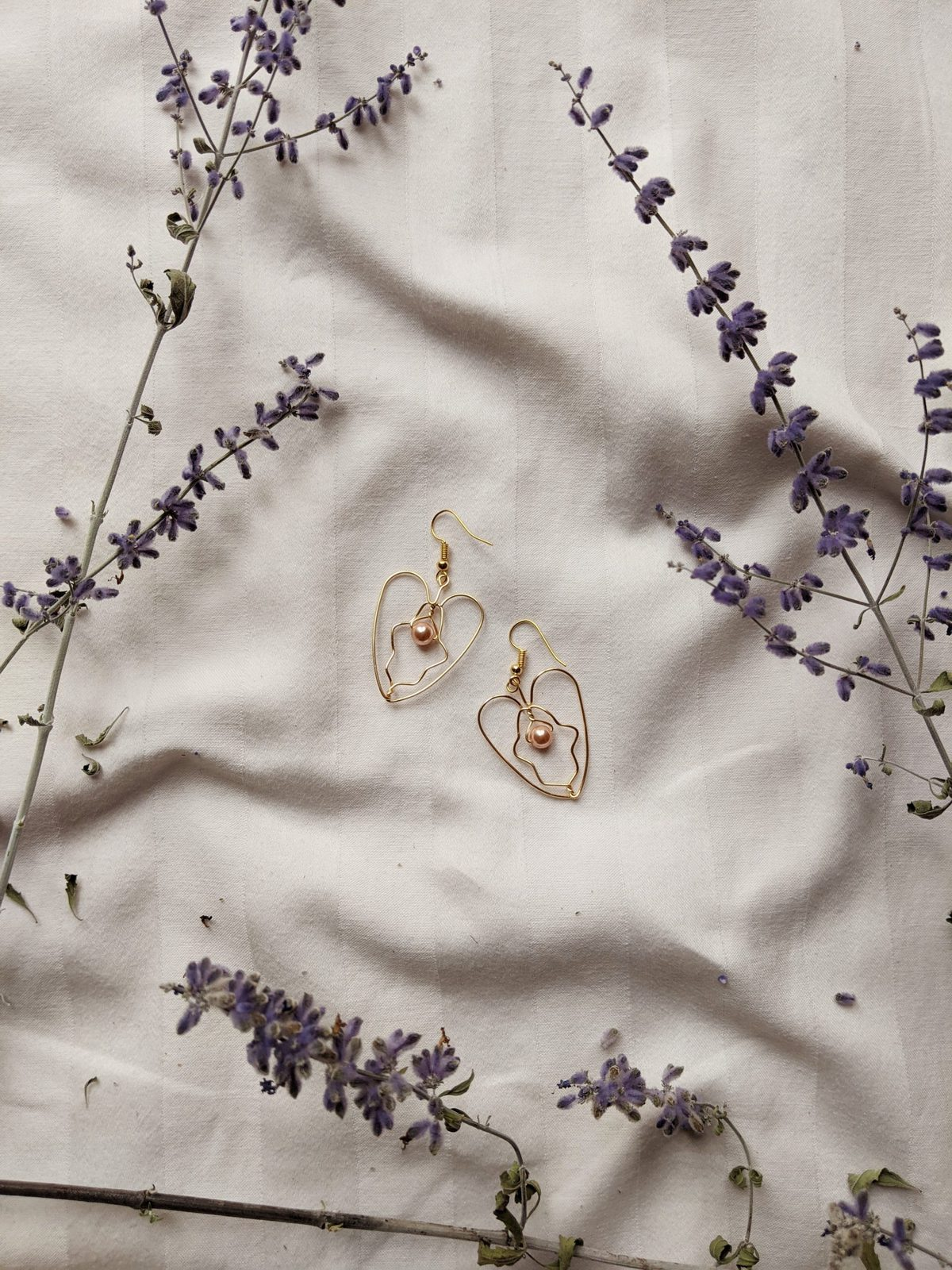 A pair of gold wire earrings on a white sheet surrounded by springs of lavender