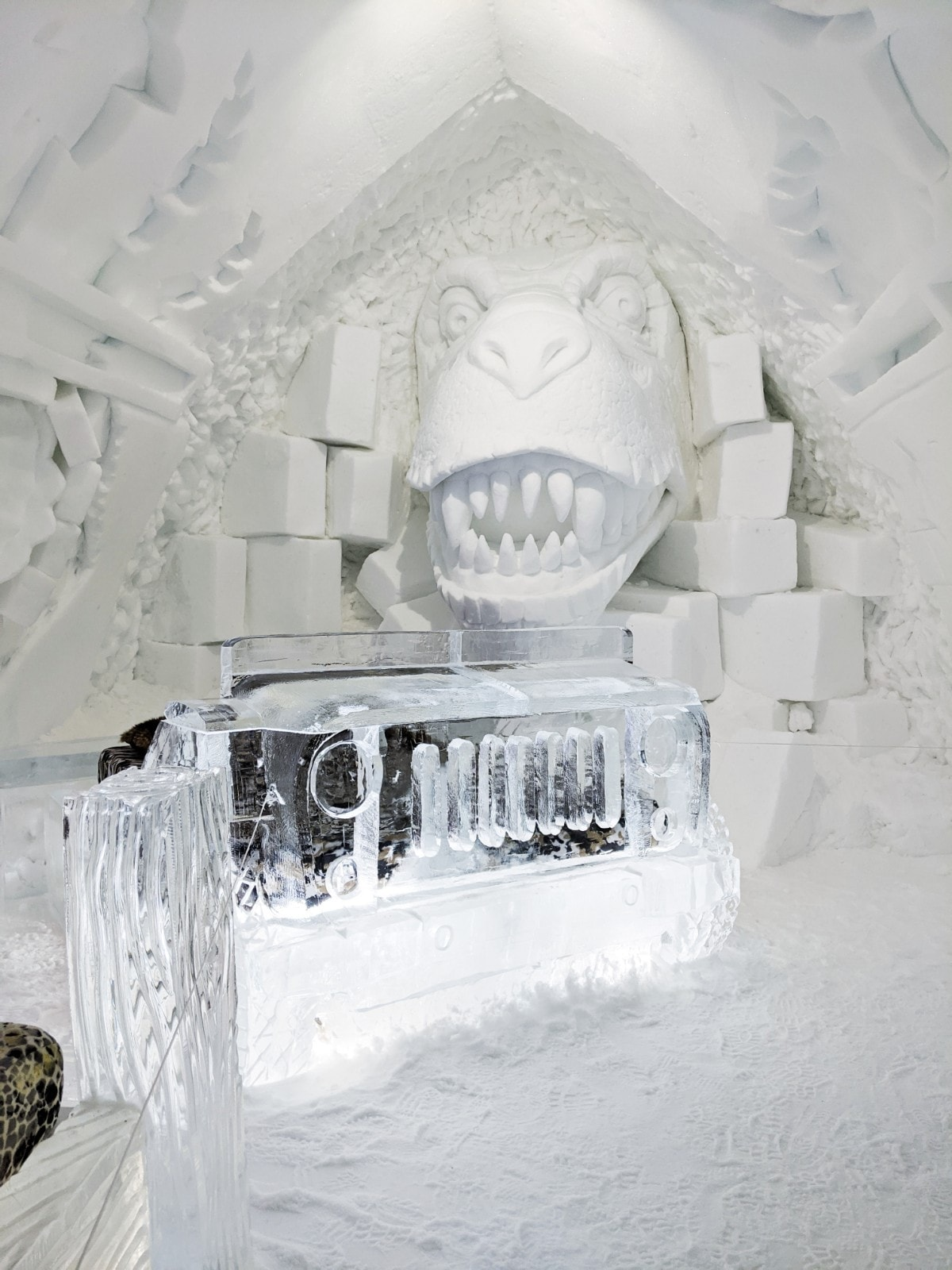 The dinosaur room with T-Rex carved into the snow, behind a truck-shaped bed made of ice