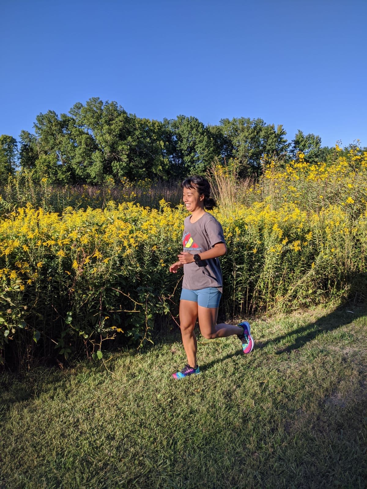 me running in a grass field with a blue sky and lots of yellow flowers in the background