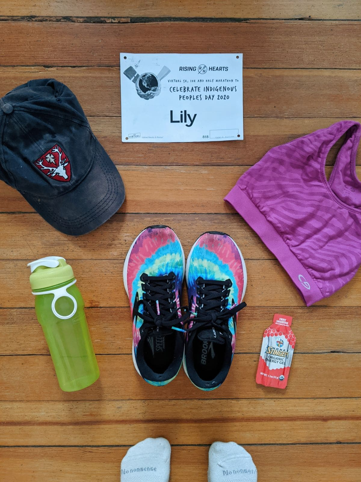 flatlay of running gear with a baseball cap, shoes, gel, sports bra, water bottle, and race bib