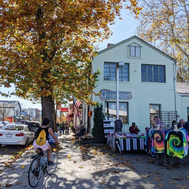 The town of Yellow Springs in the fall with a yellow-leaf tree on the left and a mint building on the right with people selling tie dye shirts