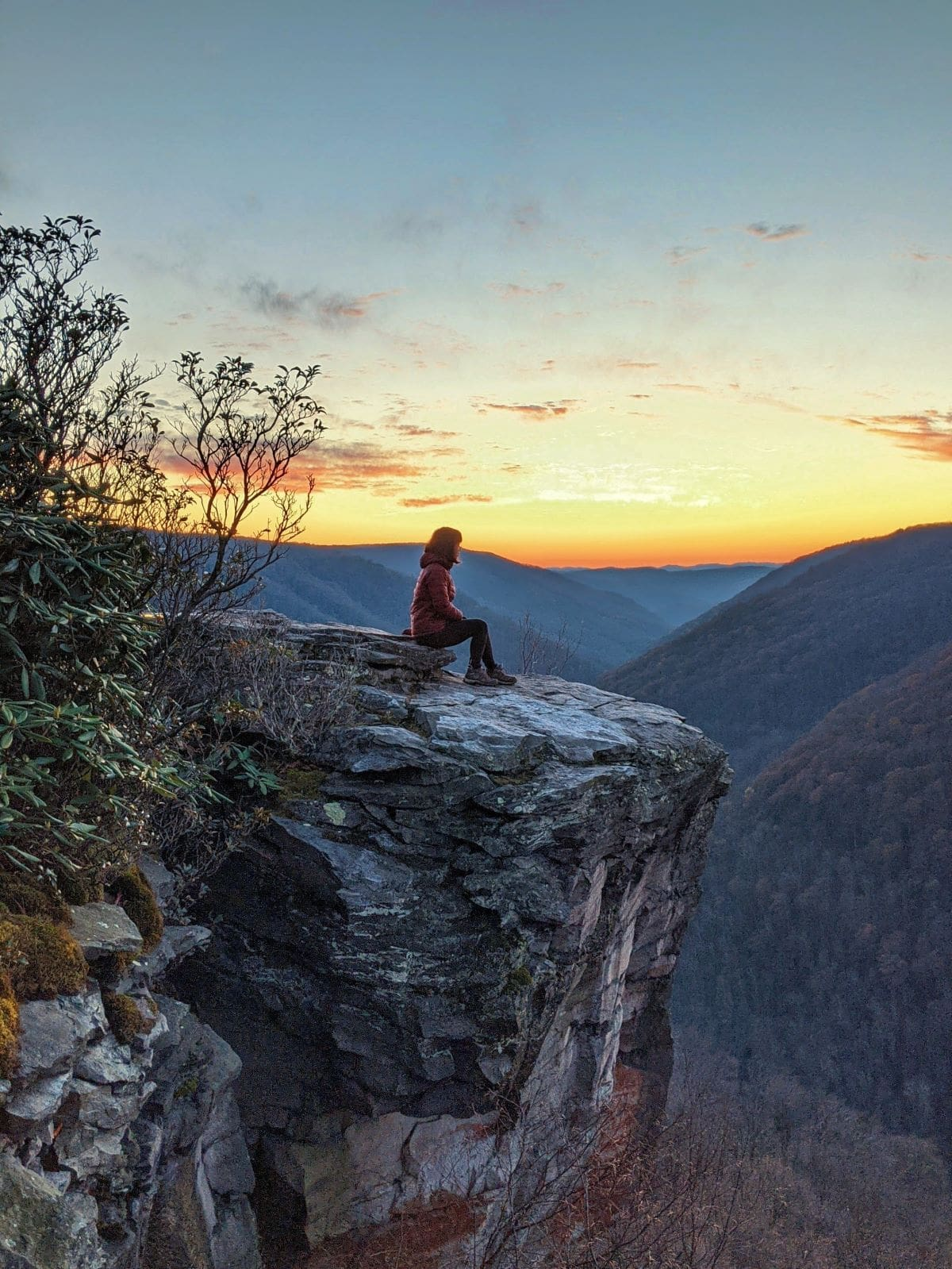 me sitting on a ledge overlooking some mountains at sunset