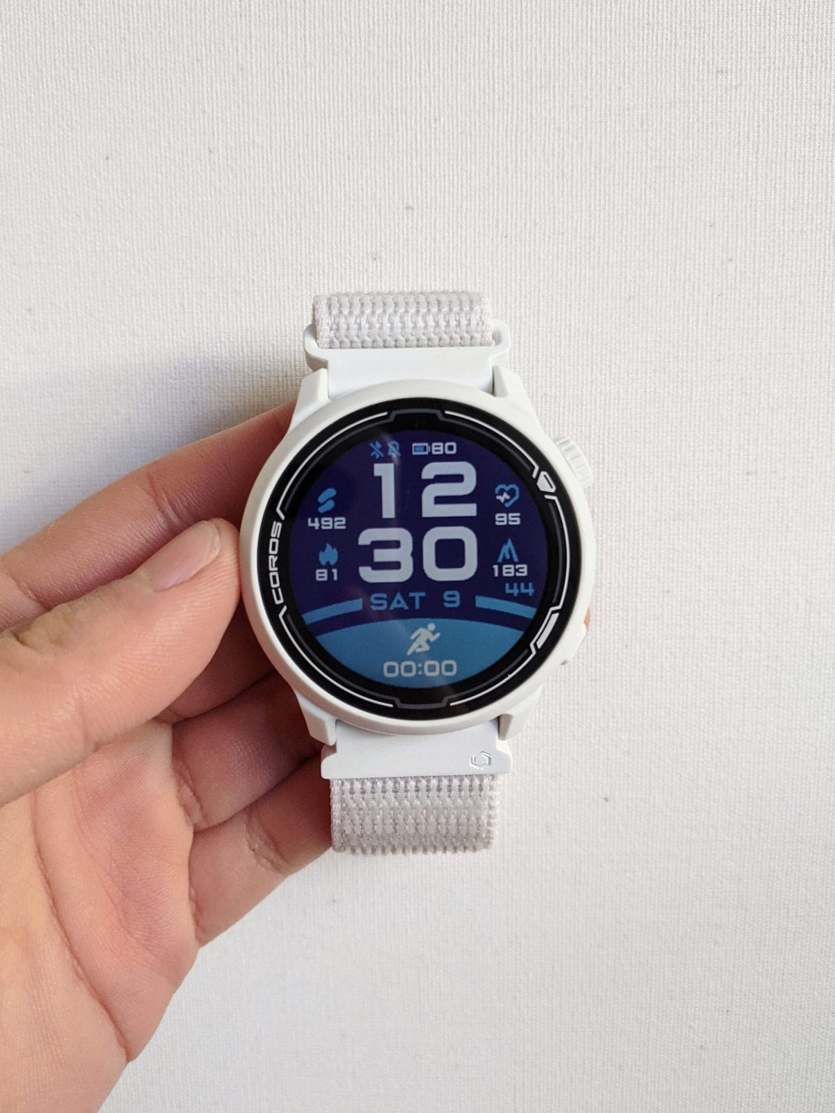 Coros Pace 2 in white with a nylon band with the default blue watch face