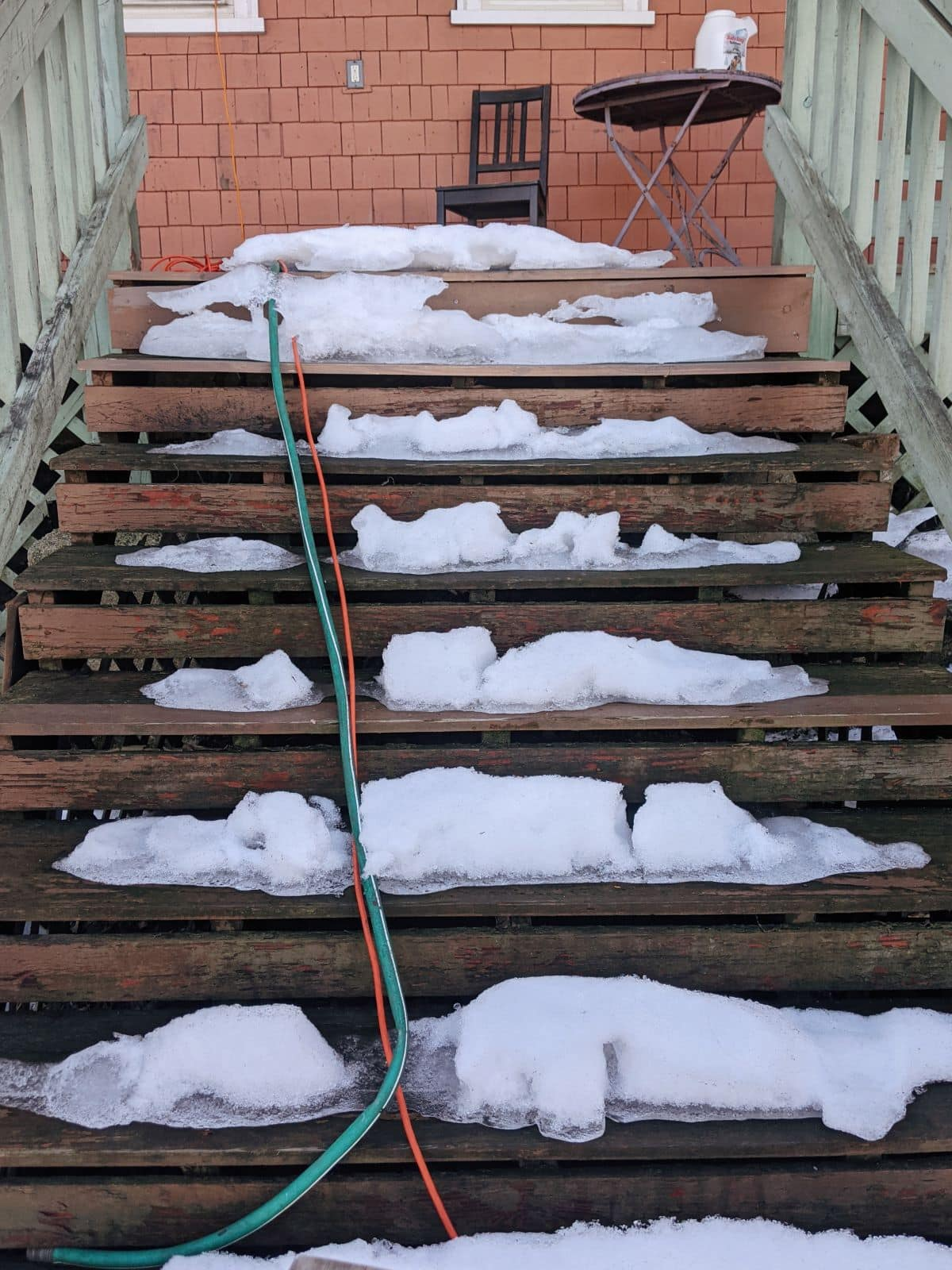 old wooden deck stairs covered in snow