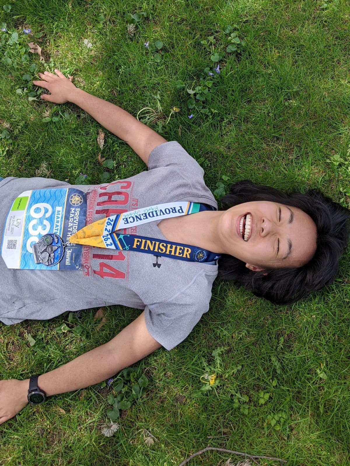 lying on the grass after the Providence Marathon
