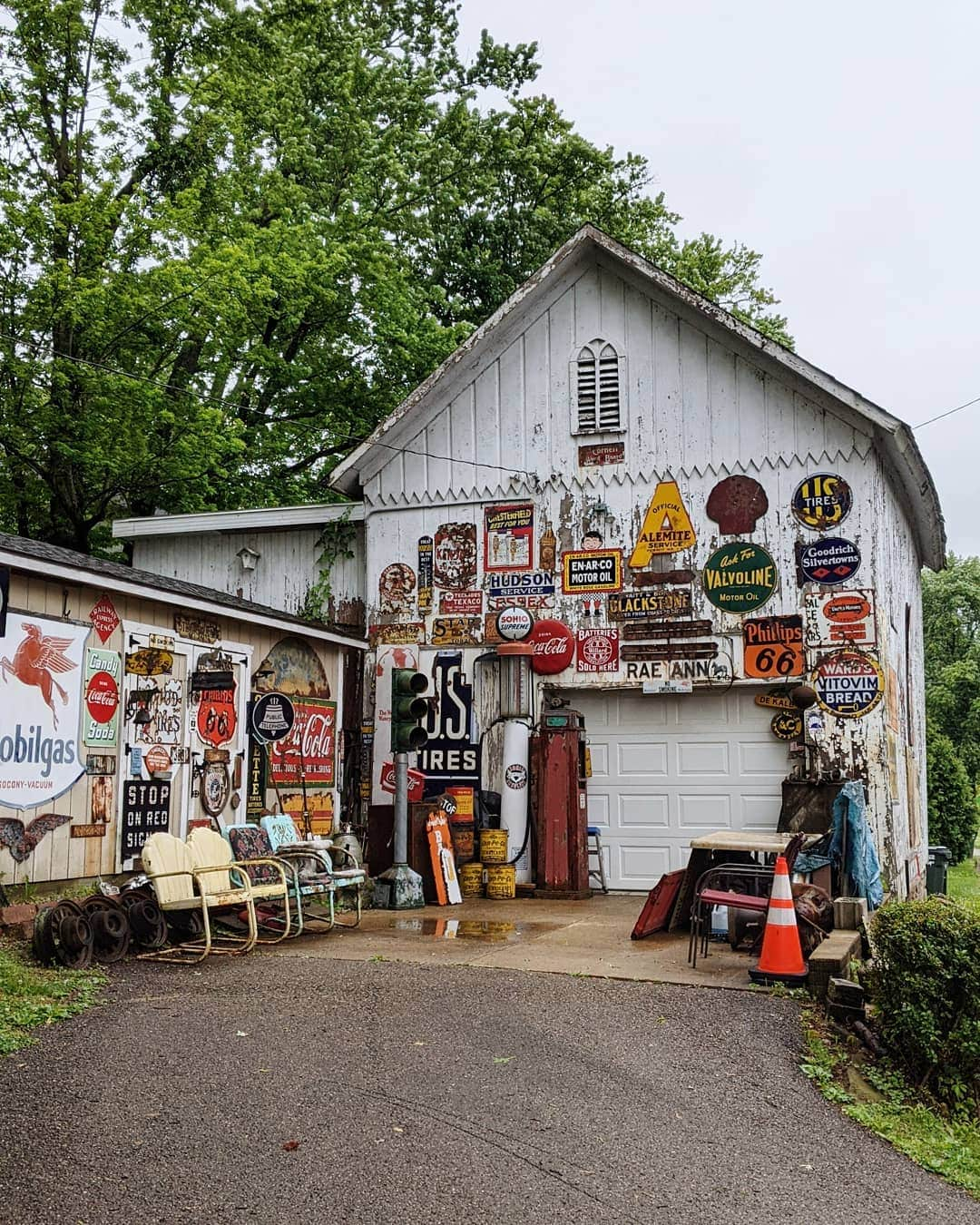 Old white garage covered in vintage signs