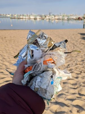 a handful of soft plastics and wrappers on the beach