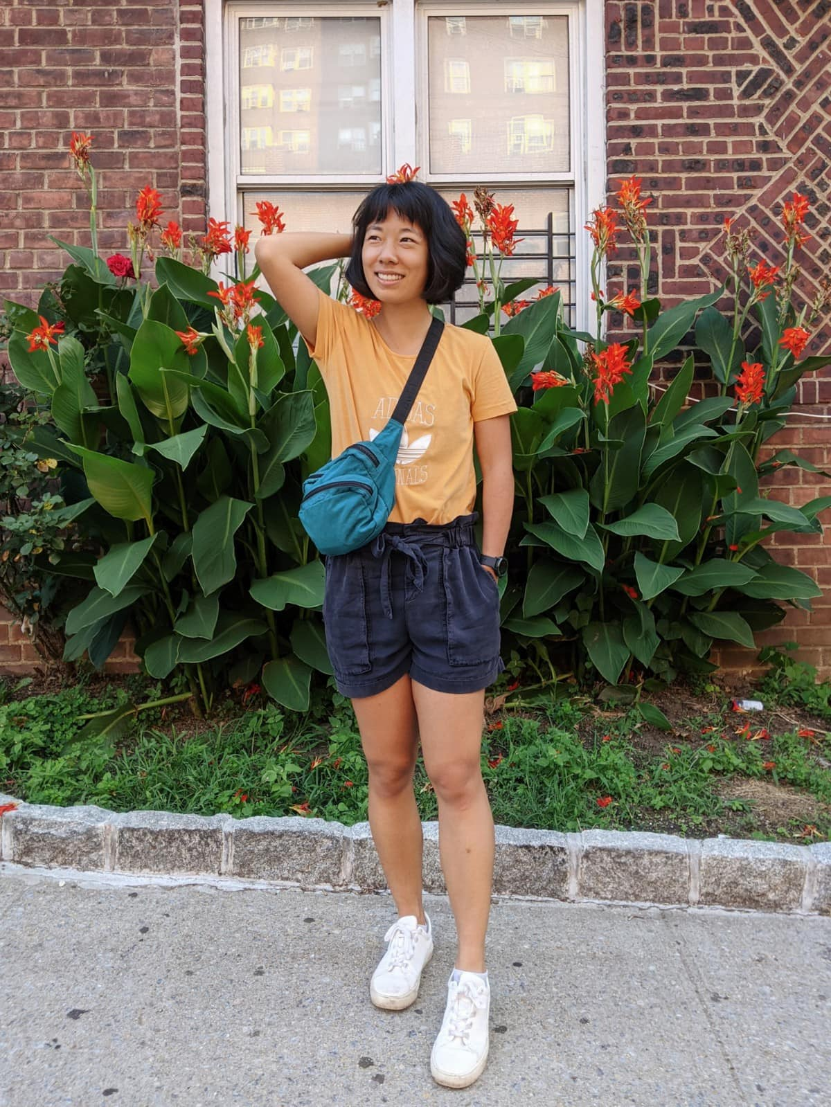 Me wearing a thrifted mustard Adidas tshirt and thrifted navy paper bag shorts with a teal fanny pack as a side body bag, standing in front of large flowers