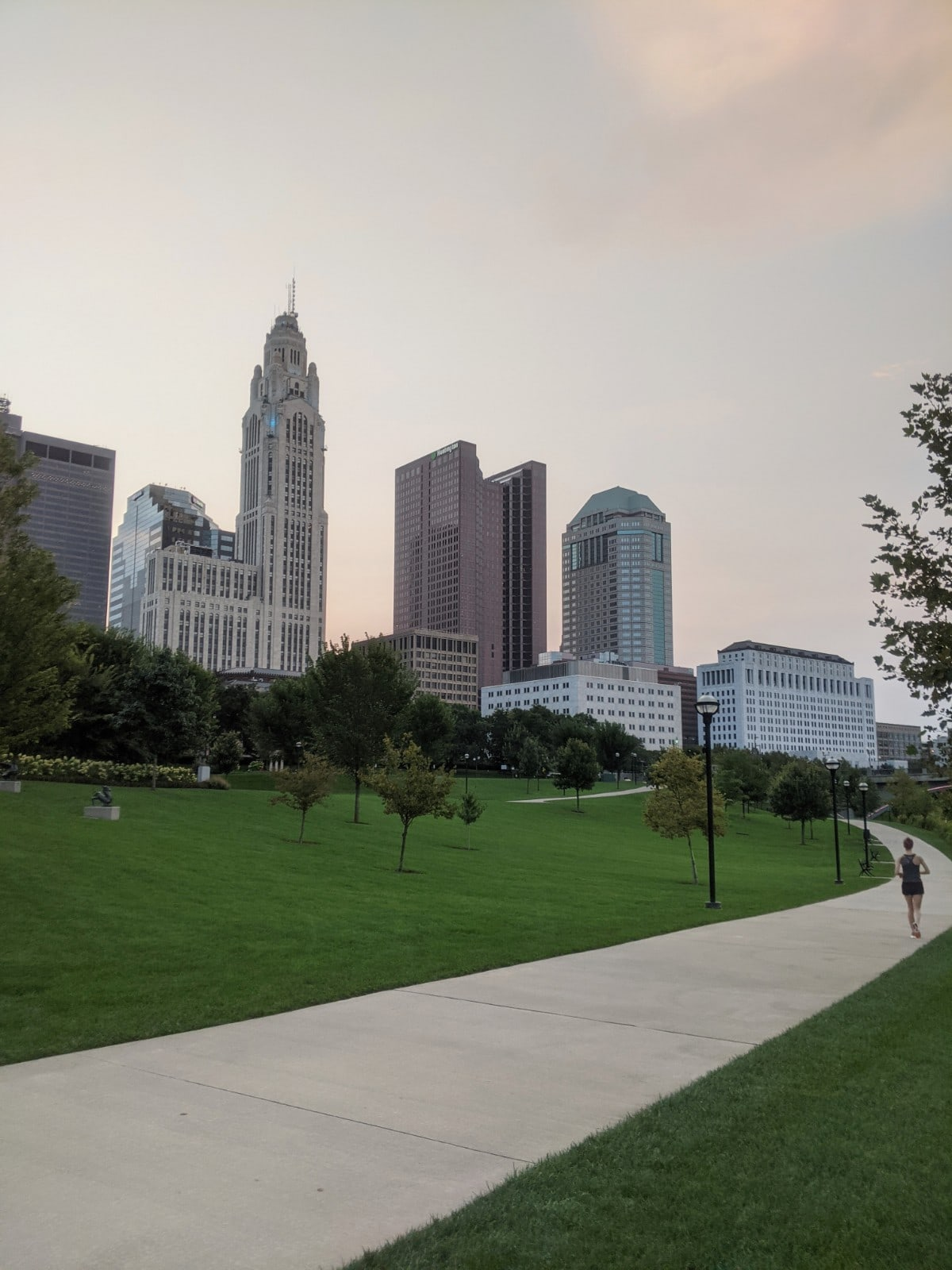 the Columbus skyline, viewed up-close from the Scioto Mile walking path with a runner in the distance